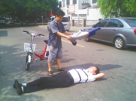 大叔骑电动车摔倒昏迷 过路小伙为他扇风降温