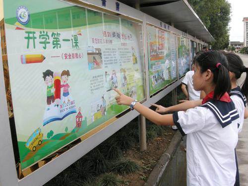 开学第一天,同学们在校园宣传栏前观看《开学第一课——安全在我心》