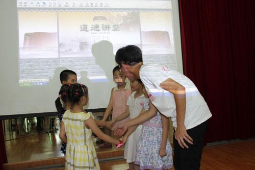 图为小朋友们跟着大学生在学习文明礼仪.图片