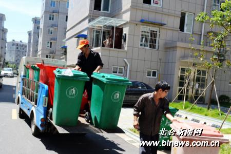 图为清洁工正在将垃圾桶搬上清运车