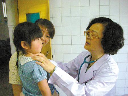 杨春雨/图为杨春雨医生在为患病女童做检查。(记者朱和风摄)