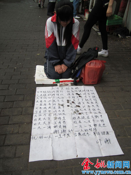 姚寻/6月12日早上,在下菱菜场南门口,一个穿着校服的女孩跪在地上...