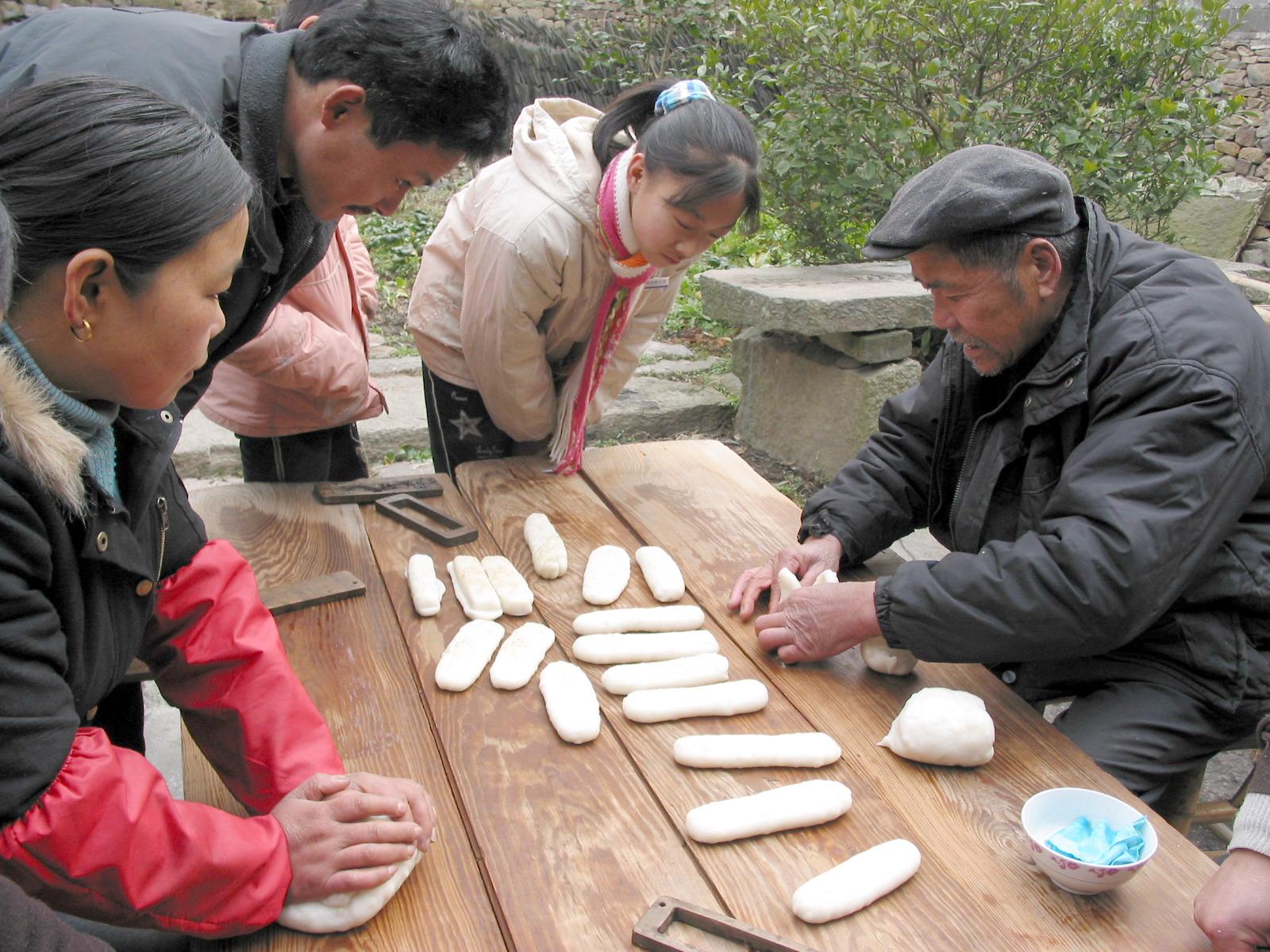 慈城水磨年糕手工制作历史悠久,迄今己有160多年历史。其以梁糊米、水底青等粳米和水为主要原料,经种植、选米、浸泡、磨粉、沥粉、擞(音为叔,意为搓)碎、蒸熟、搡舂、摘条、印糕十道工序制作而成,涉及缸、石磨、布袋、刨刀、蒸龙、捣臼和年糕板等十多种工具。