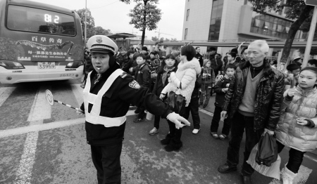 江北/江北中心小学门口,协警帮助学生、家长过马路。...