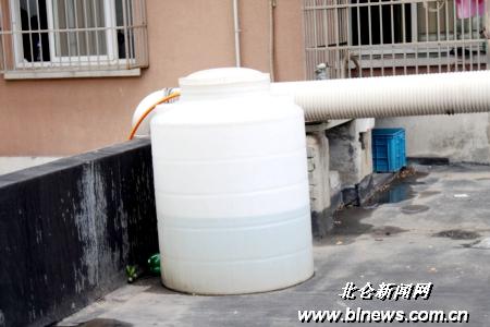 图为餐馆楼顶平台上的废油桶和油烟管