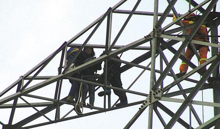 疑男友出轨赤脚爬上电塔 民警40米高空救援轻生女