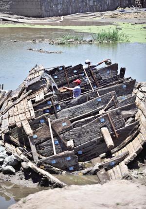 工作人员用水浇湿船木使其保持潮湿,防止开裂.记者崔引摄