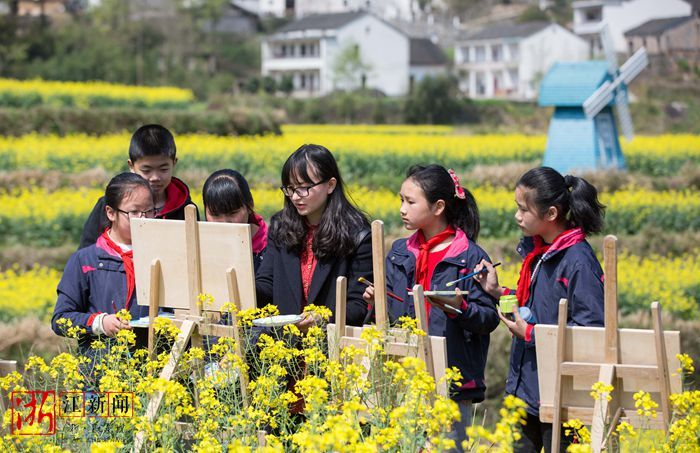 大堰学校的学生们跟着老师在油菜花地里采风画画.