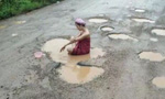 为解决路面积水问题 她在水坑中洗了个澡
