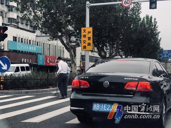 宁波街头文明一幕:白衣男士下车扶老人过马路 无人鸣笛