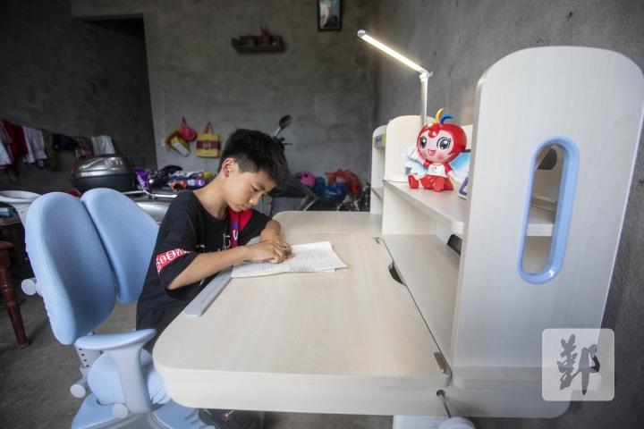图为救助学子用上新学习桌。