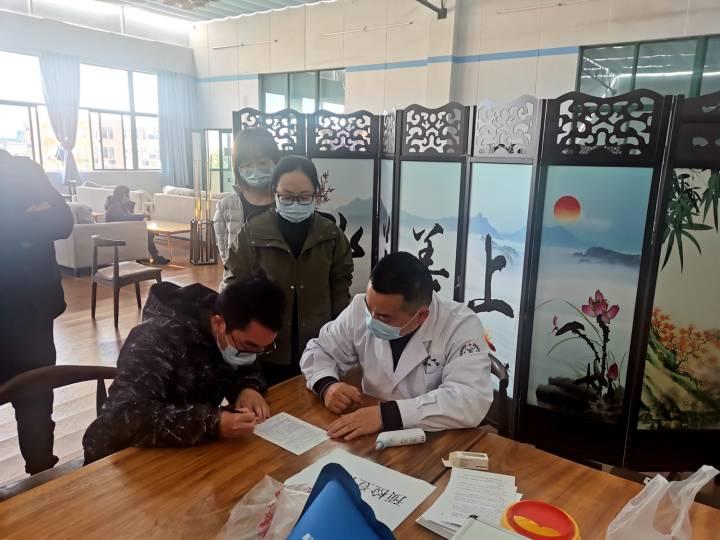 咸祥中学接种点-接种者在告知书上签名.JPG